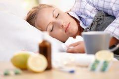Junge Frau fing das kalte Legen beim Bettschlafen ab Stockbild