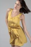 Junge Frau in flüssigem gelbem Kleid Stockfoto