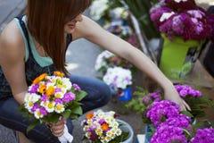 Junge Frau am Floristen Shop Stockfoto