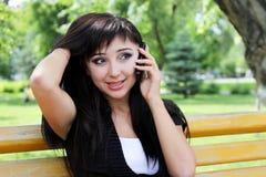 Junge Frau am Frühlingspark sprechend am Telefon. Stockfotos