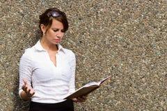 Junge Frau frustriert mit den Anmerkungen in ihrem Zeitschriftennotizbuch lizenzfreies stockbild