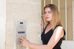 Junge Frau am Gebäudewechselsprechanlagentelefon in der Straße stockfotografie