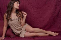 Junge Frau gegen Burgunder-Hintergrund Stockfoto