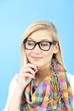 Junge Frau gegen den blauen Hintergrund Stockbilder