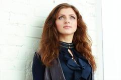 Junge Frau gegen die weiße Wand, die oben schaut Lizenzfreie Stockbilder