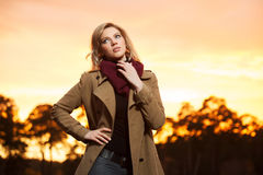 Junge Frau gegen ein Sonnenunterganglicht Lizenzfreies Stockfoto