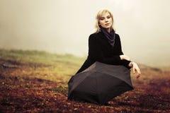 Junge Frau gegen eine nebelige Landschaft des Morgens Stockbild