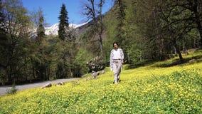 Junge Frau geht auf ein grünes Feld mit blühenden Blumen an einem Sommertag stock video footage