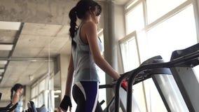 Junge Frau geht auf eine Tretmühle an der Turnhalle Herz Übungen in der Turnhalle stock video