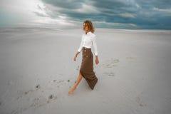 Junge Frau geht barfuß in Wüste auf Himmelhintergrund Lizenzfreie Stockfotos