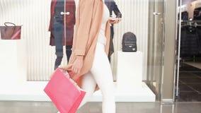 Junge Frau geht entlang ein Showfenster mit Taschen und Telefon in ihrer Hand im Einkaufszentrum Seitenansichttransportwagen gesc stock video