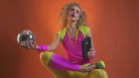 Junge Frau gekleidet in der Retrostilkleidung, einen Discoball und eine Kassette in ihren Händen beim Tanzen halten mit ihr stock video footage