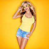 Junge Frau in gelben Tanktop und Augen-Gläsern Stockfotos