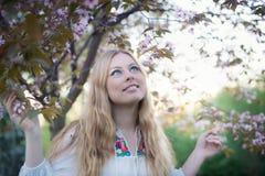 Junge Frau genießt die Glättung durch den Kirschbaum Lizenzfreie Stockbilder