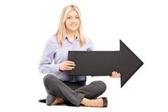 Junge Frau gesetzt auf dem Boden, der einen schwarzen Pfeil zeigt auf Th hält Lizenzfreie Stockbilder
