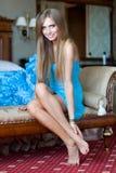 Junge Frau gesetzt auf einem Sofa Stockbild