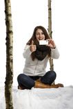 Junge Frau gesetzt im Schnee, der ein Foto macht Lizenzfreie Stockfotos