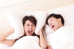 Junge Frau gestört durch die Schnarcher ihres Ehemanns Stockbilder