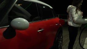 Junge Frau gestoppt, um etwas Gas auf einer Tankstelle nachts zu erhalten stock footage