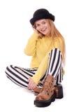 Junge Frau in gestreiften Hosen und im schwarzen Hut Stockbild