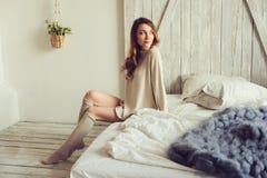Junge Frau in gestrickter Wolljacke und warme Socken wachen morgens im gemütlichen skandinavischen Schlafzimmer und im Sitzen auf Lizenzfreie Stockbilder