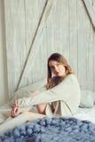 Junge Frau in gestrickter Wolljacke und warme Socken wachen morgens im gemütlichen skandinavischen Schlafzimmer und im Sitzen auf Stockbilder