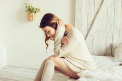 Junge Frau in gestrickter Wolljacke und warme Socken wachen morgens im gemütlichen skandinavischen Schlafzimmer und im Sitzen auf Lizenzfreies Stockfoto