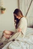 Junge Frau in gestrickter Wolljacke und warme Socken wachen morgens im gemütlichen skandinavischen Schlafzimmer und im Sitzen auf Stockfotos