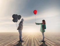 Junge Frau gibt einen roten Ballon Stockfotografie