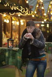 Junge Frau am Gl�hweinstand | young woman drinks glogg. A dark haired woman drinks glogg at the market stall stock photos