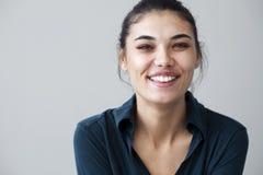 Junge Frau glücklich auf grauem Hintergrund Stockfoto