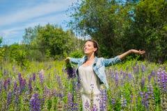 Junge Frau, glücklich, Stellung unter dem Feld von violetten Lupines, lächelnd, purpurrote Blumen Blauer Himmel auf dem Hintergru Lizenzfreies Stockfoto