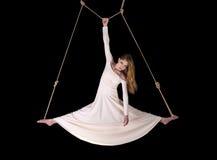 Junge Frau Gymnast im weißen Kleid auf Seil Stockfoto