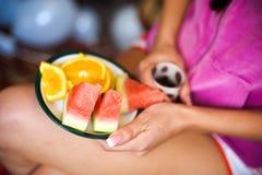 Junge Frau hält eine Platte mit Wassermelonen und Orangen lizenzfreie stockbilder