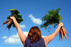 Junge Frau hält eine rote Rübe und eine Karotte herein gegen einen blauen Himmel Stockfotos