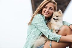 Junge Frau hält Hund draußen Stockfotos