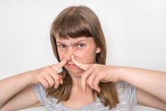 Junge Frau hält ihre Nase - Konzept des schlechten Geruchs stockfotos