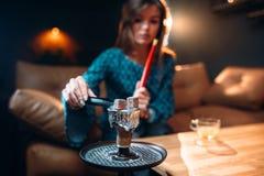 Junge Frau hält Kohle mit den Zangen und raucht Huka Stockfotografie