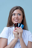 Junge Frau hält Kreditkarten an und lächelt Stockfoto