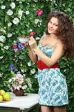 Junge Frau hält Platte mit Erdbeeren und zeigt eine Beere Lizenzfreie Stockfotografie