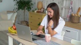 Junge Frau hält Schale, setzt sie auf Tabelle, fortfährt, am Laptop, Zeitlupe zu arbeiten stock footage