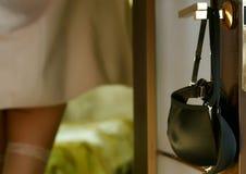 Junge Frau hängt einen BH auf dem Türgriff Mädchen in den Strümpfen und Tuch im Hotelzimmer lizenzfreies stockbild
