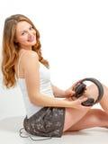 Junge Frau hört froh auf Audio Stockbild