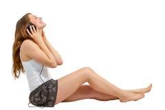 Junge Frau hört froh auf Audio Stockfoto