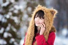 Junge Frau am Handy draußen in der Winterzeit Stockbilder