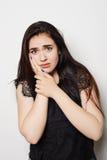 Junge Frau hat eine Zahnschmerzen, Studiofoto auf einem grauen Hintergrund Stockfotografie
