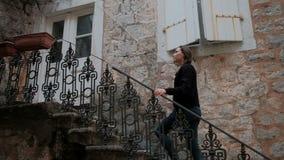 Junge Frau in heftigen Jeans herauf die Metallleiter vom Steinhaus stock video