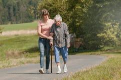 Junge Frau hilft der älteren Frau, die mit Stock geht stockfotos