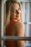 Junge Frau hinter Fenster Lizenzfreie Stockbilder