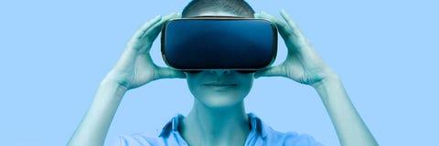 Junge Frau in ihrem 30s unter Verwendung der Schutzbrillen der virtuellen Realit?t Frau, die VR-Kopfhörer lokalisiert über blauer stockbilder